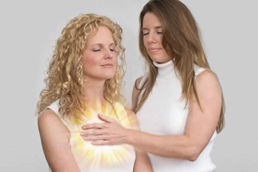 Quantum-Touch practisioner using healing energy on a womans heart chakra